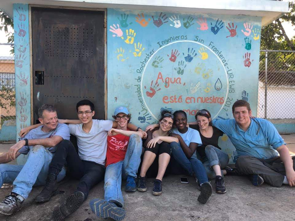 Members of the Engineers Without Borders team take a break in front of the blue shed that houses water disinfection.